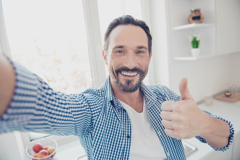 Homme gai attirant dans le studio à carreaux occasionnel a de lumière de chemise image stock