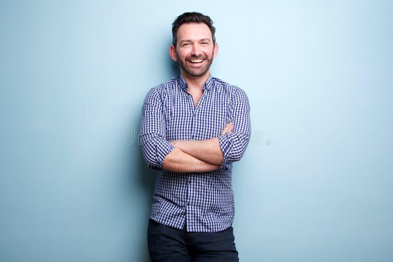 Homme gai avec la barbe posant contre le mur bleu avec des bras croisés photo libre de droits