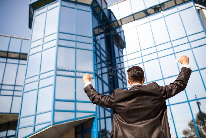 Homme gai d'affaires célébrant l'extérieur de succès de son bureau avec les mains rised image libre de droits