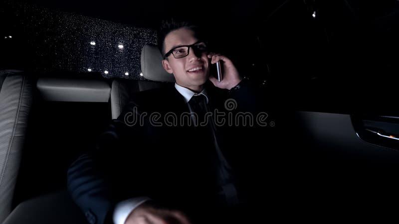 Homme gai dans le costume parlant au téléphone avec l'amie, s'asseyant dans la voiture, chemin de la maison photos stock
