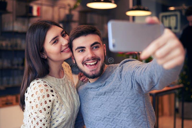 Homme gai faisant le selfie avec son amie au café photographie stock libre de droits