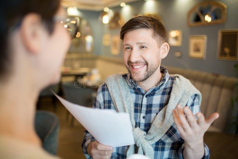 Homme gai parlant au collègue au sujet des papiers photos libres de droits