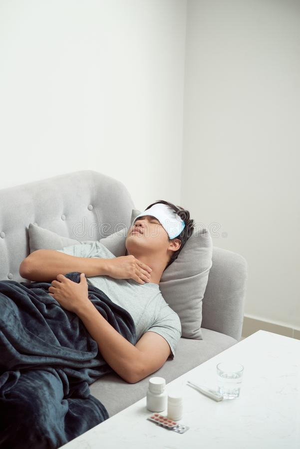 Homme gaspill? malade se situant dans le virus de grippe de froid et d'hiver de douleur de sofa ayant des comprim?s de m?decine d photo libre de droits