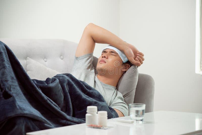 Homme gaspill? malade se situant dans le virus de grippe de froid et d'hiver de douleur de sofa ayant des comprim?s de m?decine d image libre de droits