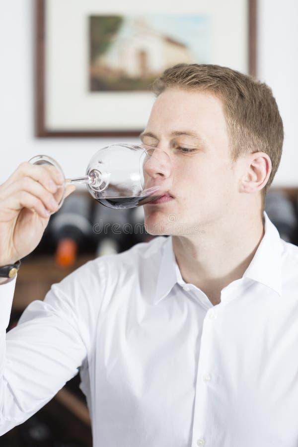 Homme go?tant une glace de vin rouge photo stock