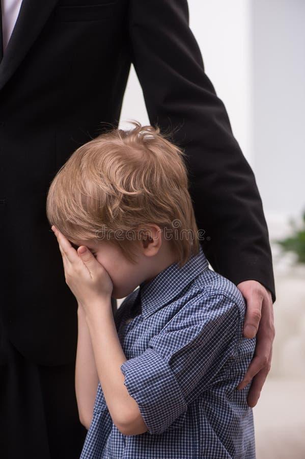 Homme grand étreignant le garçon pleurant photos libres de droits
