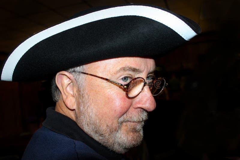 Homme Greyhaired avec le chapeau à trois cornes et le sourire en verre et astucieux rond image stock
