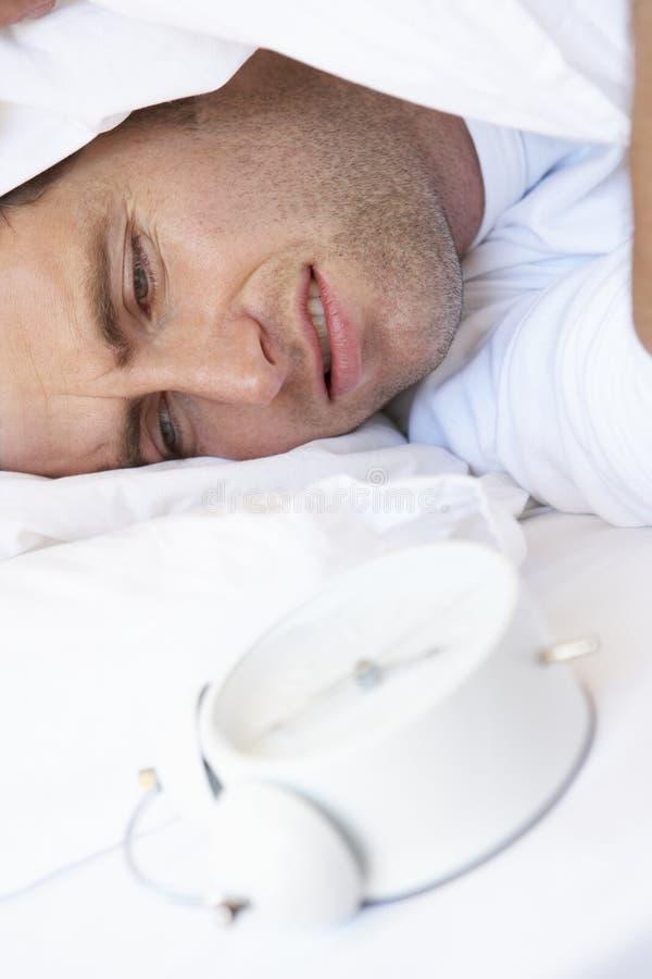 Homme grincheux dans le lit arrêtant le réveil images stock