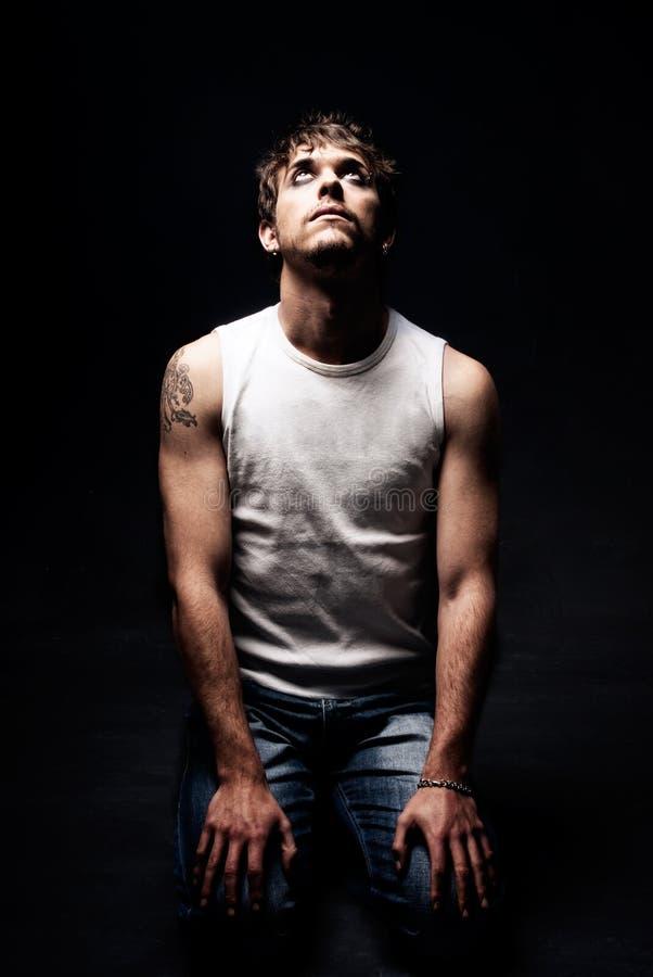 Homme grossier sur des genoux recherchant l'obscurité de tatouage sur le noir photographie stock