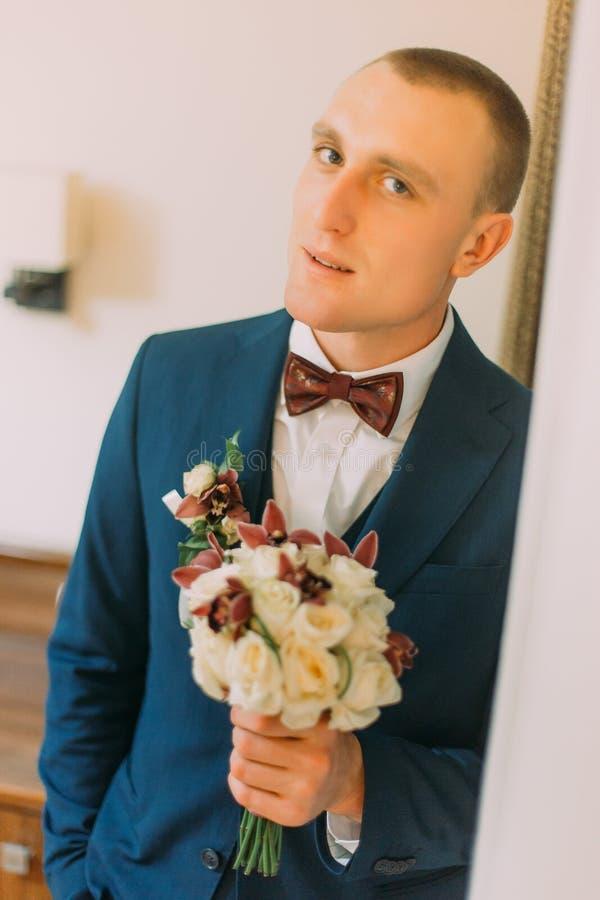Homme habillé élégant attirant tenant le bouquet élégant des roses tenant l'huisserie proche d'intérieur photo stock