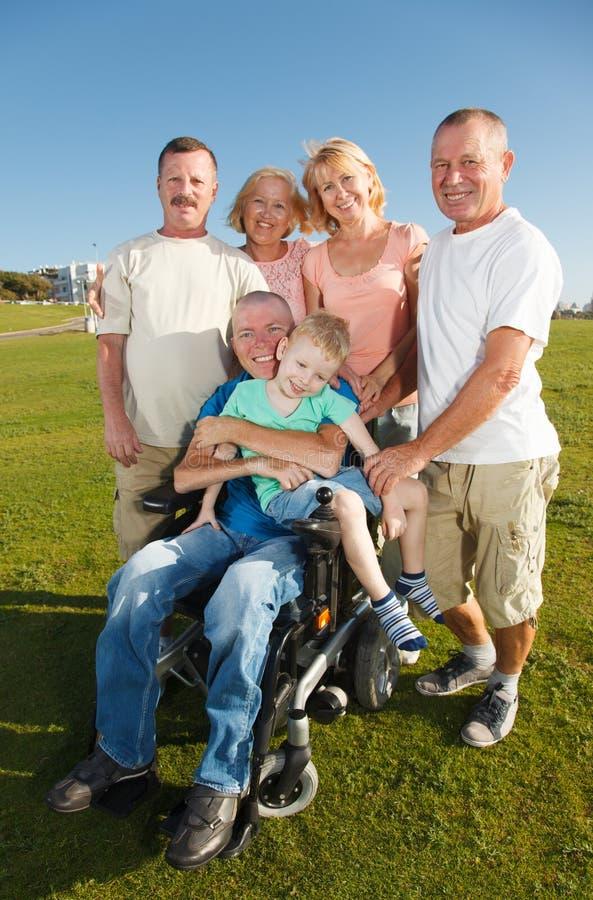 Homme handicapé avec la famille dehors photographie stock