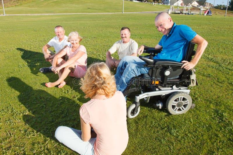 Homme handicapé avec la famille dehors photographie stock libre de droits