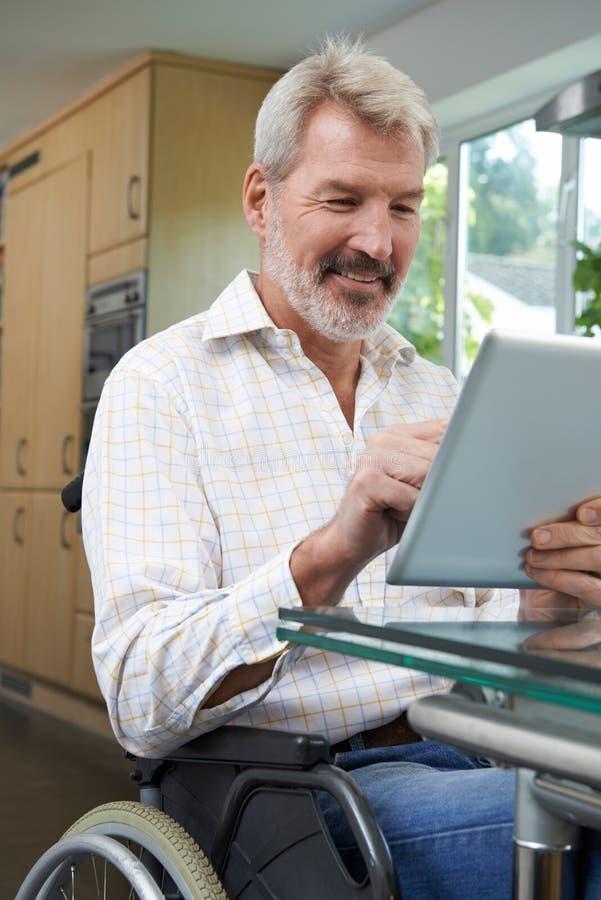 Homme handicapé dans le fauteuil roulant utilisant la Tablette de Digital à la maison image stock