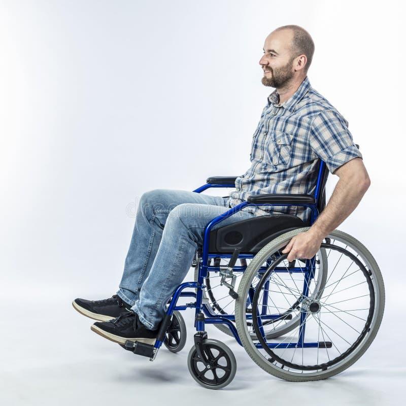 Homme handicapé de sourire s'asseyant dans un fauteuil roulant photographie stock libre de droits