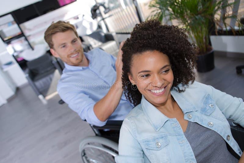 Homme handicapé habillant la belle jeune femme de cheveux photos libres de droits