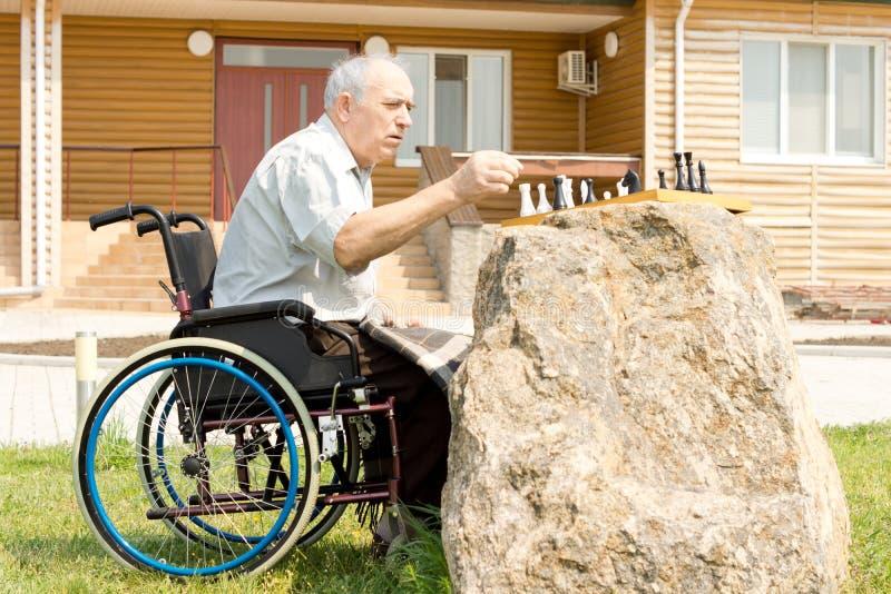 Homme handicapé jouant des échecs dans son jardin images libres de droits