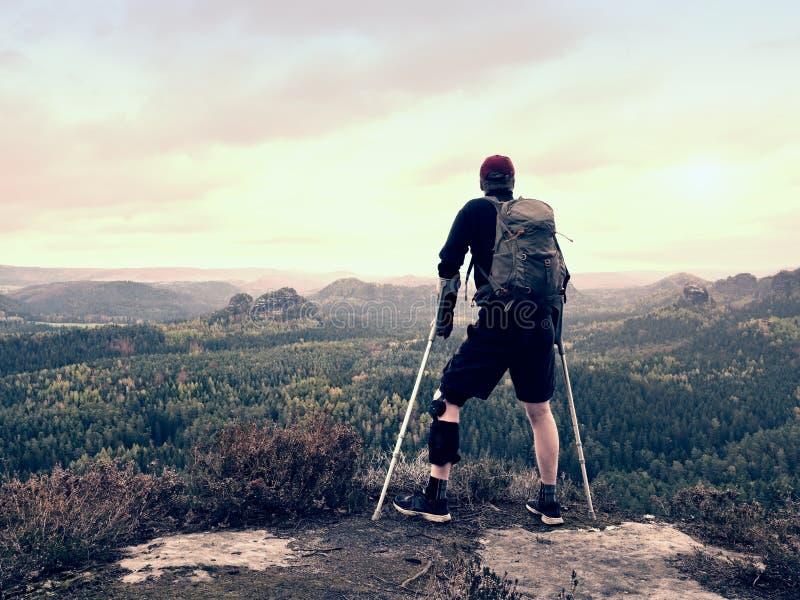 Homme handicapé sur des béquilles sur la roche Le genou blessé dans des accolades de genou en métal du néoprène et l'homme tienne photo libre de droits
