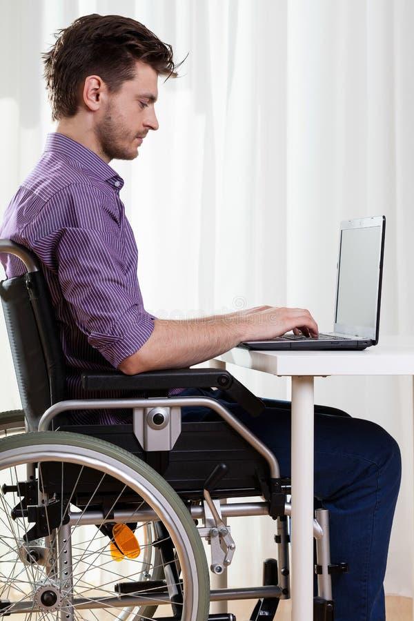 Homme handicapé surfant sur l'Internet photo stock