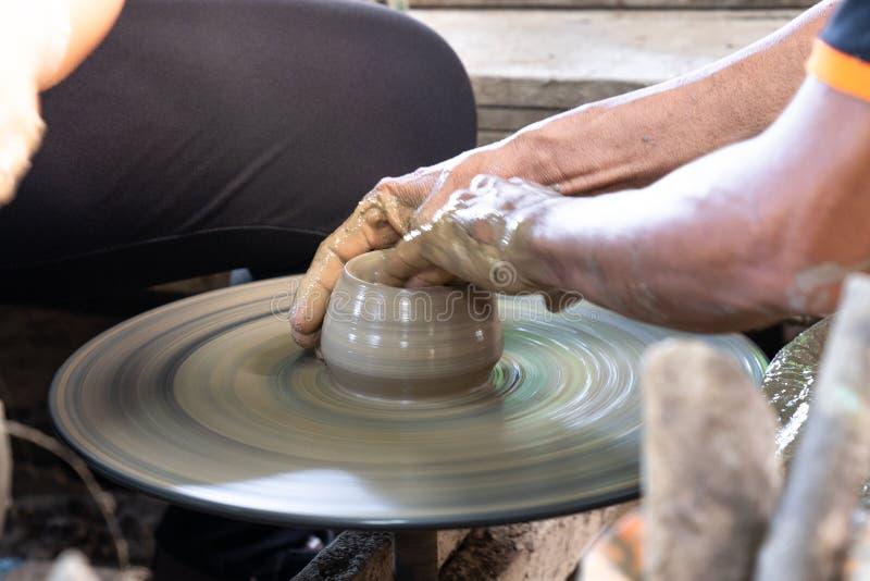 homme haut étroit de main rendant la poterie de métier en céramique photo stock