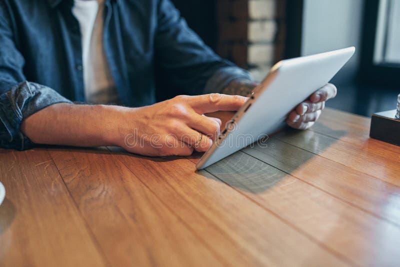 Homme haut étroit de mains utilisant le comprimé, wifi se reliant Travail juste du café photos stock