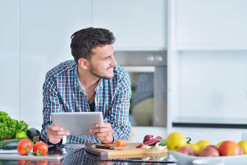 Homme heureux à l'aide du comprimé numérique dans la cuisine à la maison image libre de droits
