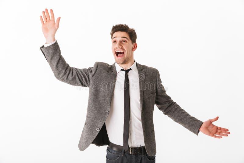 Homme heureux étonné d'affaires dans la veste ondulant sa paume images libres de droits