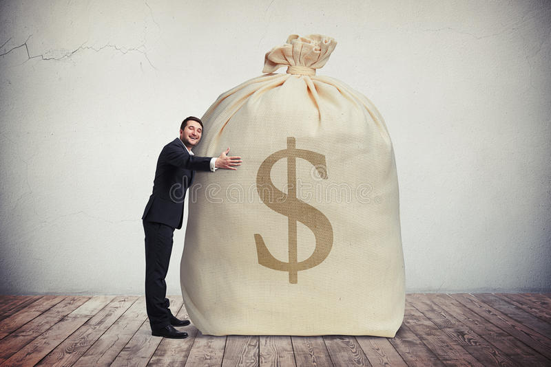 Homme heureux étreignant un grand sac d'argent photo stock