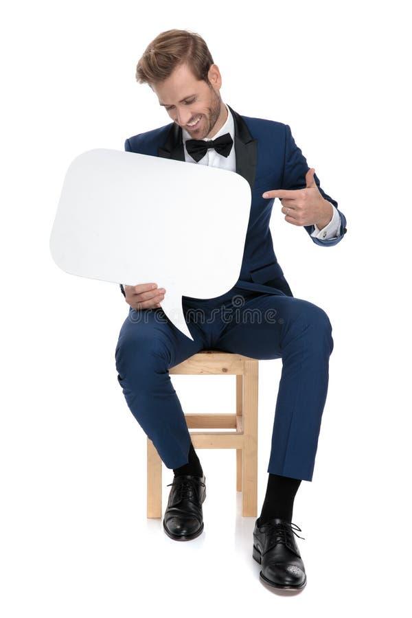 Homme heureux assis dirigeant son doigt pour masquer la bulle de la parole images libres de droits