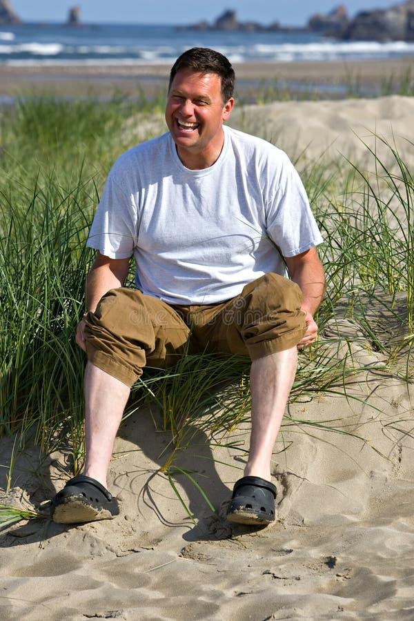 Homme heureux aux pattes blanches de plage photos stock
