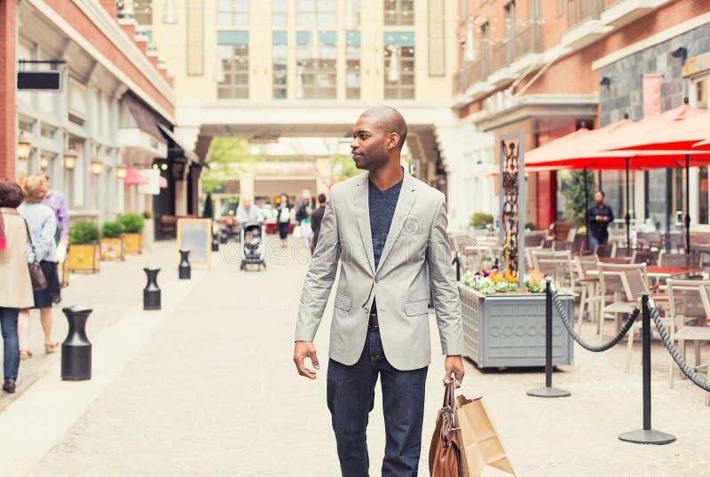 Homme heureux avec des paniers marchant sur une rue photo stock