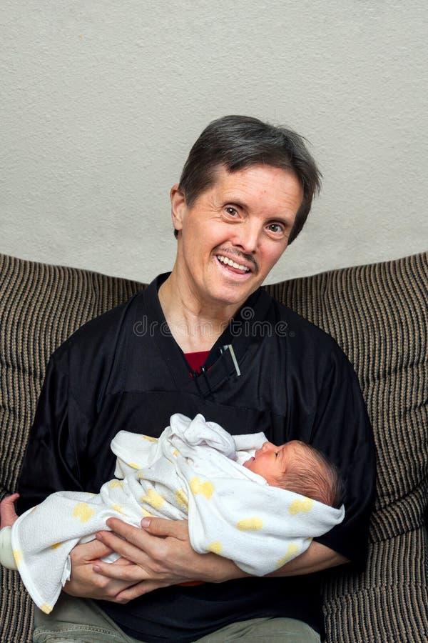 Homme heureux avec des prises Infan nouveau-né de dents de syndrome et de faux de bas images libres de droits