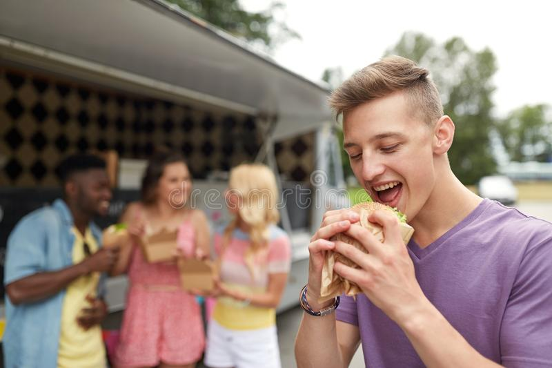 Homme heureux avec l'hamburger et les amis au camion de nourriture photos libres de droits