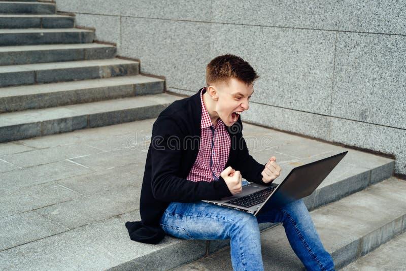 Homme heureux avec l'ordinateur portable ai fait je image libre de droits