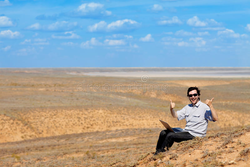 Homme heureux avec l'ordinateur portatif à l'extérieur images stock