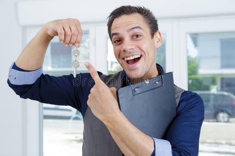 Homme heureux avec la cl? se d?pla?ant ? la nouvelle maison photos stock