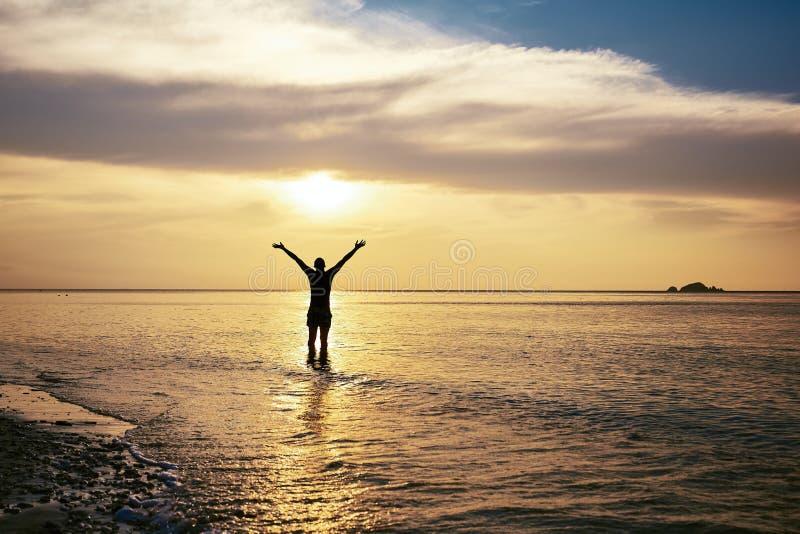 Homme heureux avec la position tendue par bras en mer photographie stock libre de droits