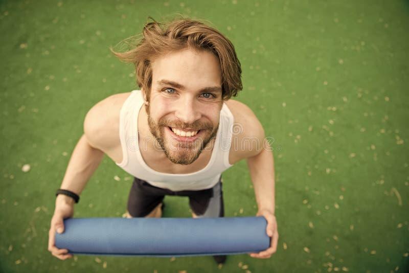 Homme heureux avec le corps musculaire tenant le tapis de yoga ou de forme physique photographie stock