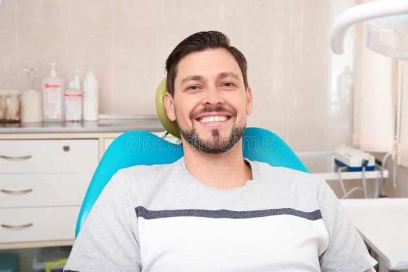 Homme heureux ayant le rendez-vous du dentiste dans la clinique photo stock