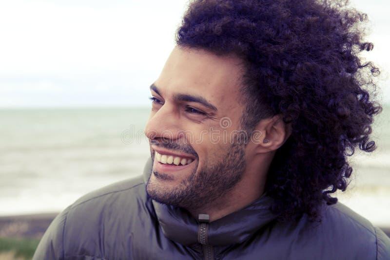 Homme heureux bel souriant en hiver devant l'océan rétro photos libres de droits