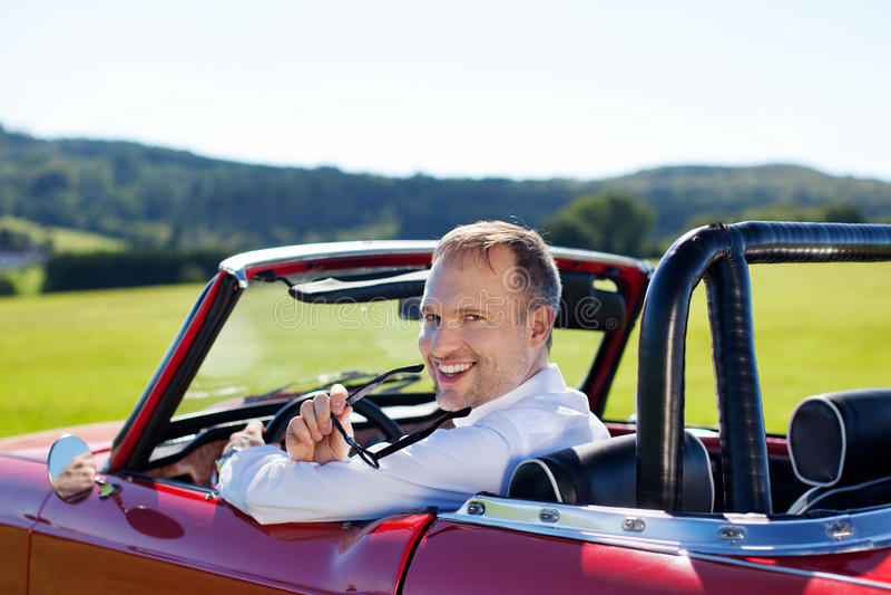 Homme heureux conduisant un cabriolet images stock