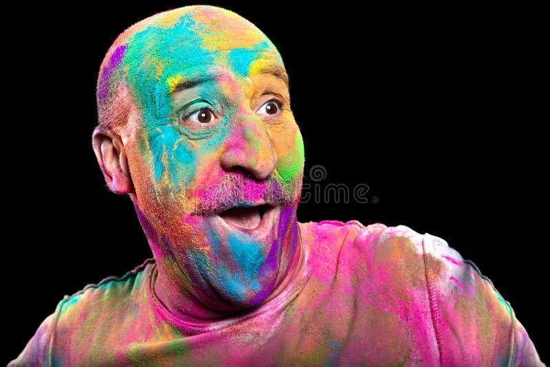 Homme heureux couvert dans la poudre brillamment color?e de Holi photographie stock