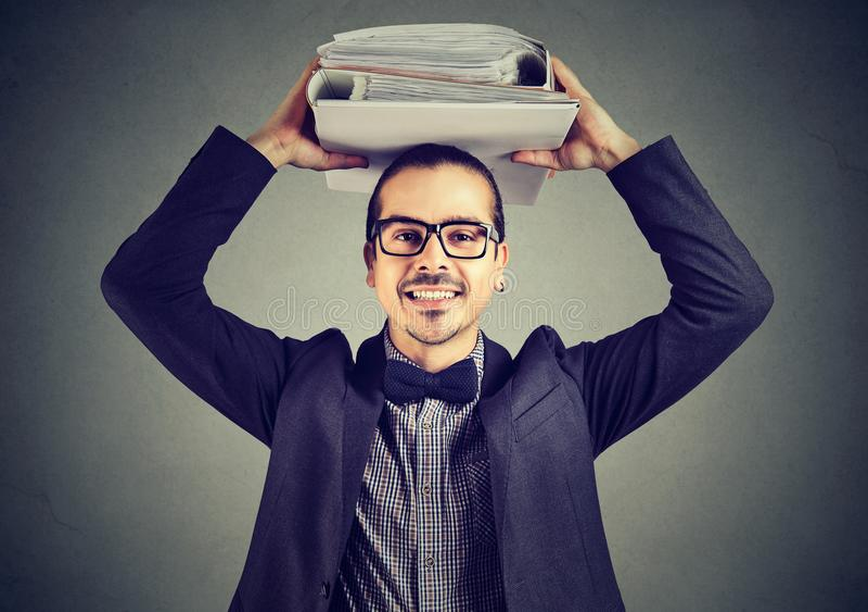 Homme heureux d'affaires avec des reliures de bureau se tenant souriantes à l'appareil-photo les équilibrant sur la tête photographie stock