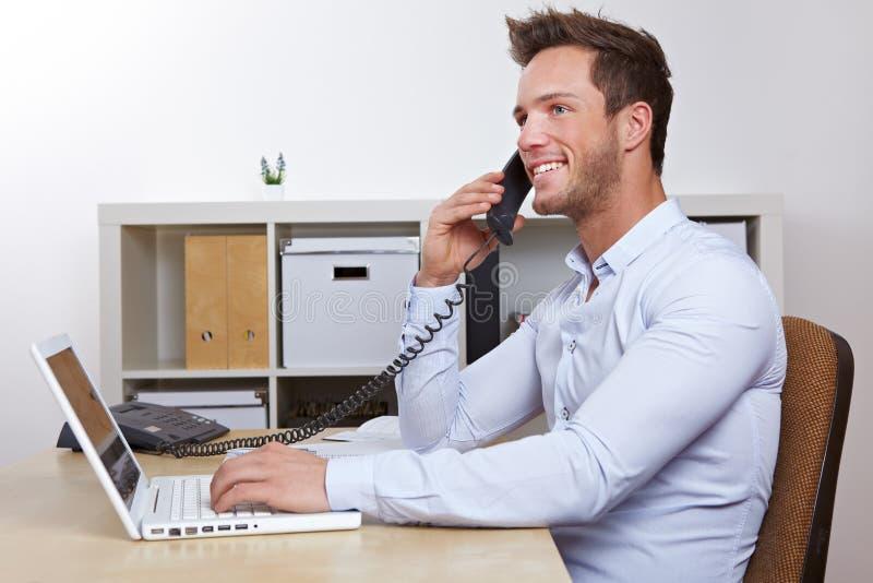 Homme heureux d'affaires dans effectuer de bureau photographie stock libre de droits