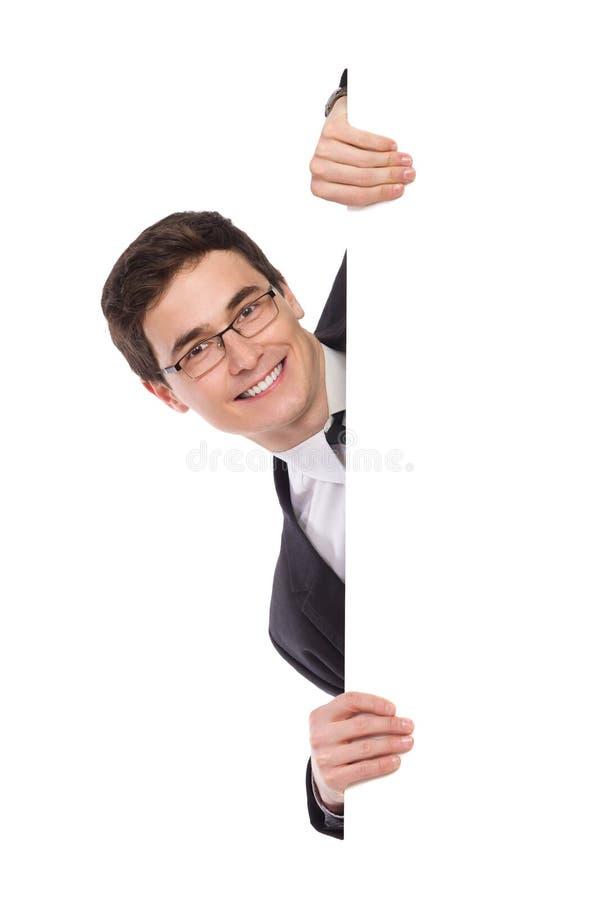 Homme heureux d'affaires jetant un coup d'oeil derrière une bannière. image stock