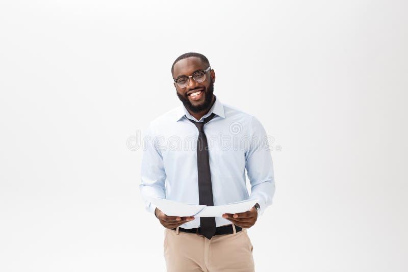 Homme heureux d'Afro-américain tenant le papier documaent au-dessus du fond blanc d'isolement avec un visage de surprise et de ch images stock