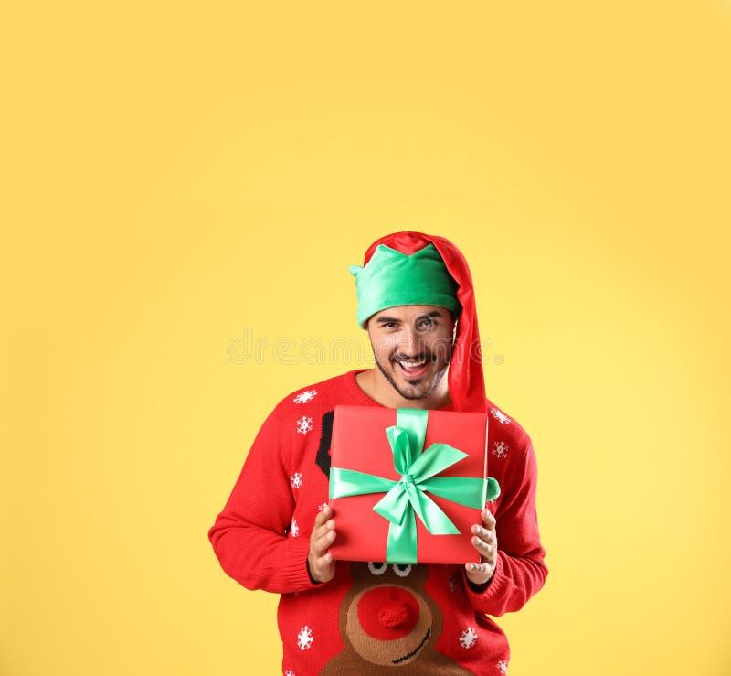 Homme heureux dans le boîte-cadeau de participation de chapeau de chandail et d'elfe de Noël sur le jaune photo stock