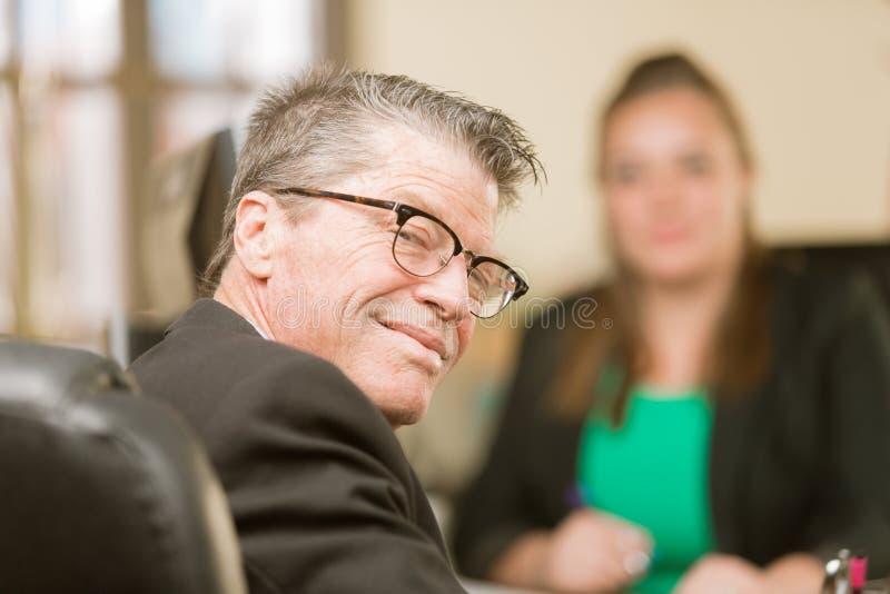Homme heureux dans le bureau avec le collègue féminin image stock