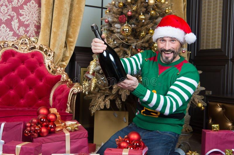 Homme heureux dans le costume d'elfe mettant la grande bouteille et le sourire photographie stock libre de droits