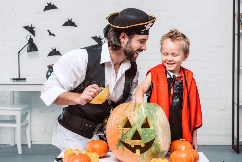 homme heureux dans le costume et le fils de pirate dans le costume de Halloween de vampire avec le potiron ensemble images stock