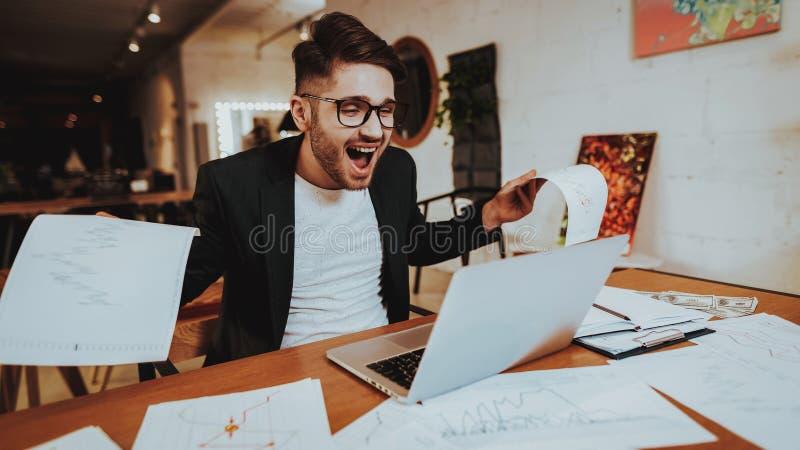 Homme heureux dans le regard noir de costume au moniteur d'ordinateur portable photos stock